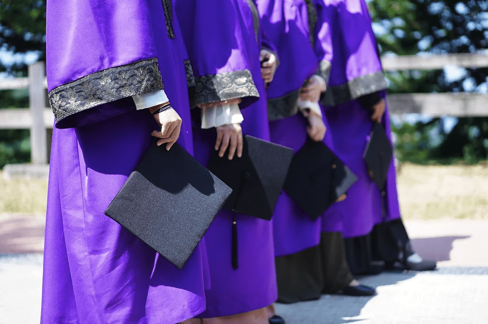 A photo of university graduates wearing purple robes hold their cap while posing together  | Photo: Pixabay
