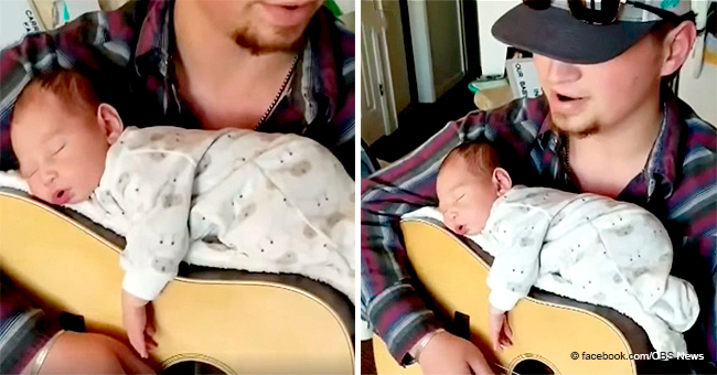 Country-Singing Father Lullabies His Newborn Daughter with His Guitar Playing While She Is on It
