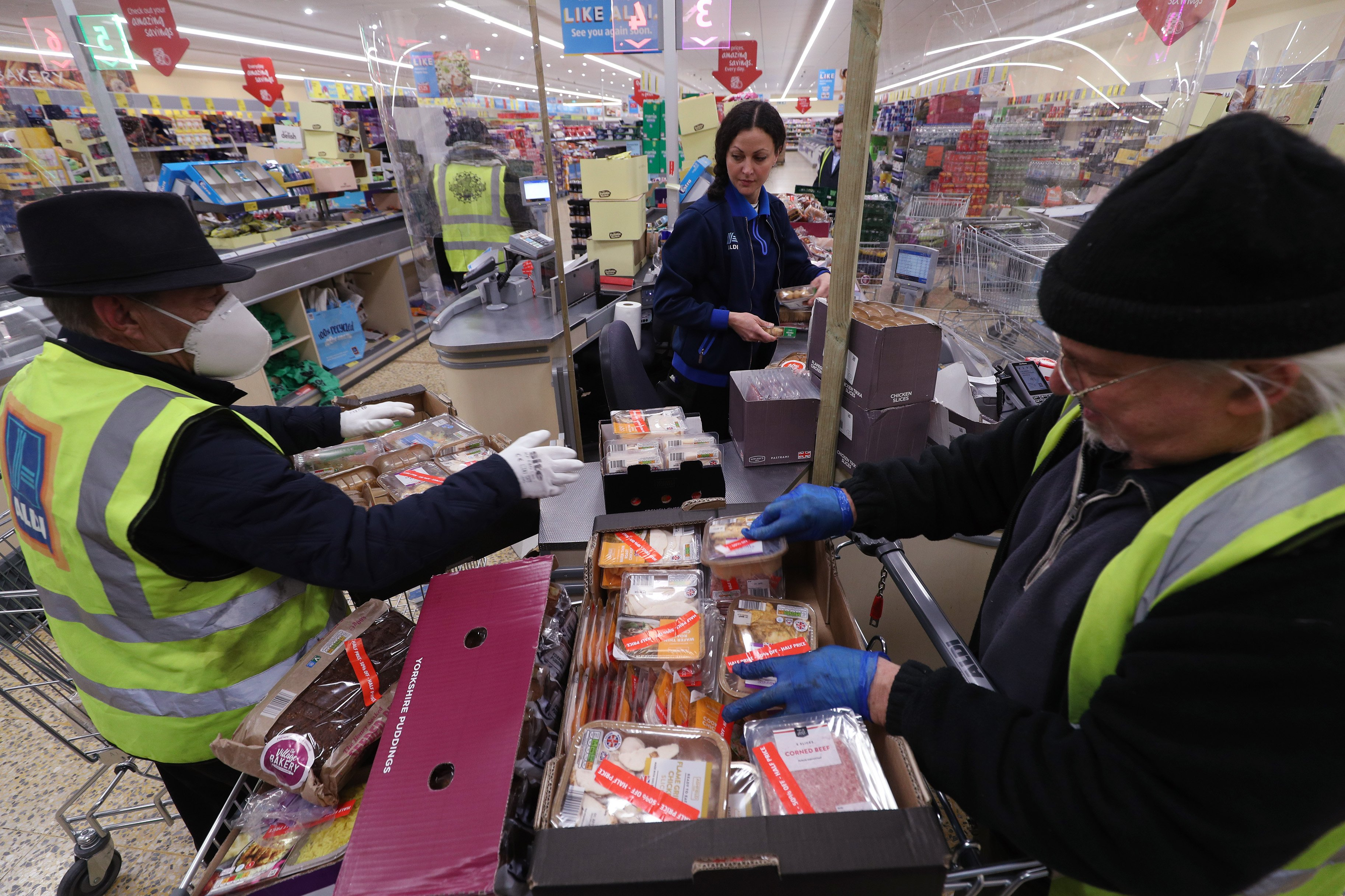 Food items being packaged at an Aldi Supermarket in London during the COVID-19 pandemic. | Photo: Getty Images.