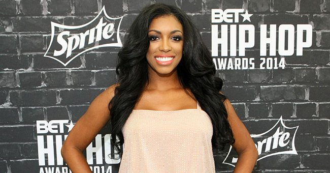 RHOA Star Porsha Williams Looks Regal Posing in Feathered off-Shoulder Dress with a Deep Slit