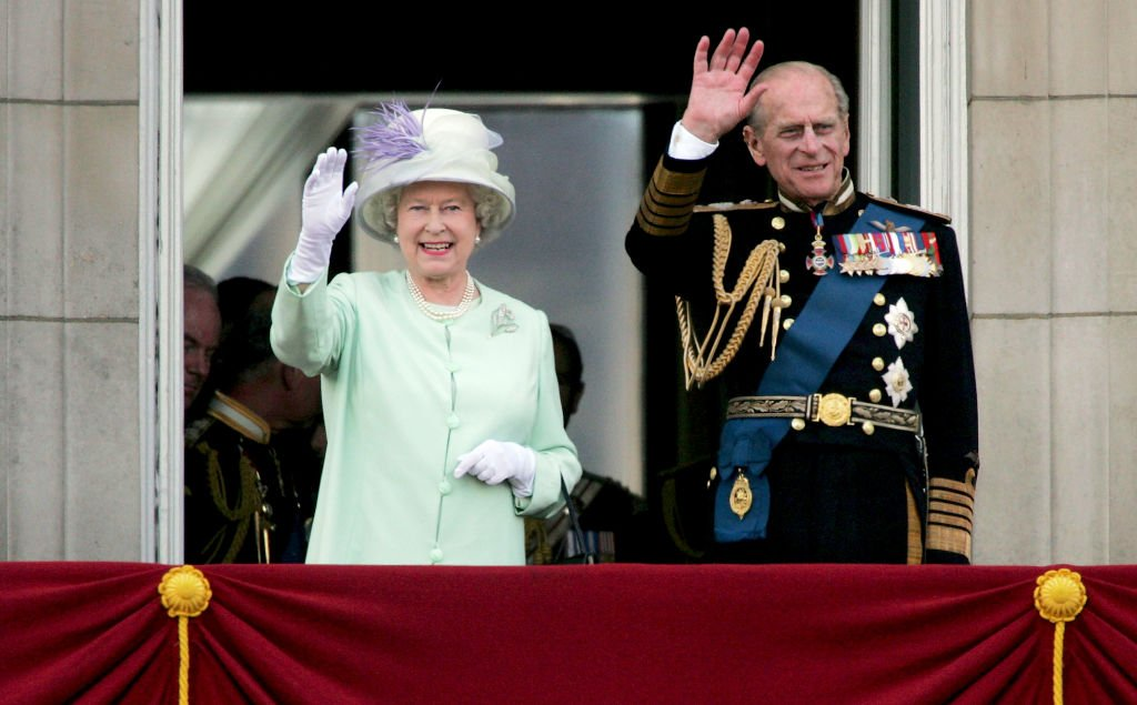 Queen Elizabeth II and Prince Philip wave to the public from the Buckingham Palace balcony on National Commemoration Day July 10, 2005 | Photo: Getty Images