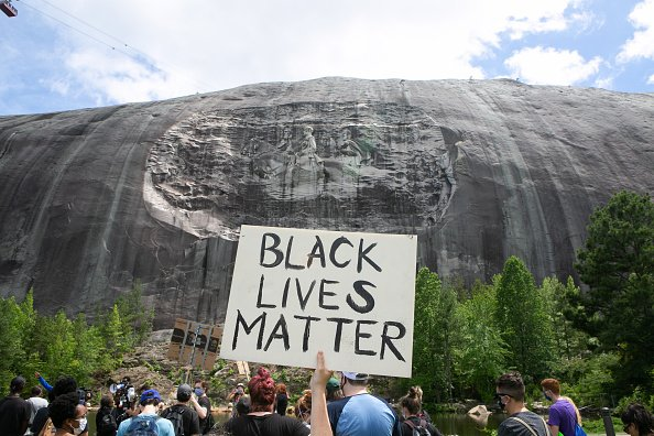 A protester holds a Black Lives Matter sign in front of the Confederate carving in Stone Mountain Park on June 16, 2020 in Stone Mountain, Georgia.   Photo: Getty Images