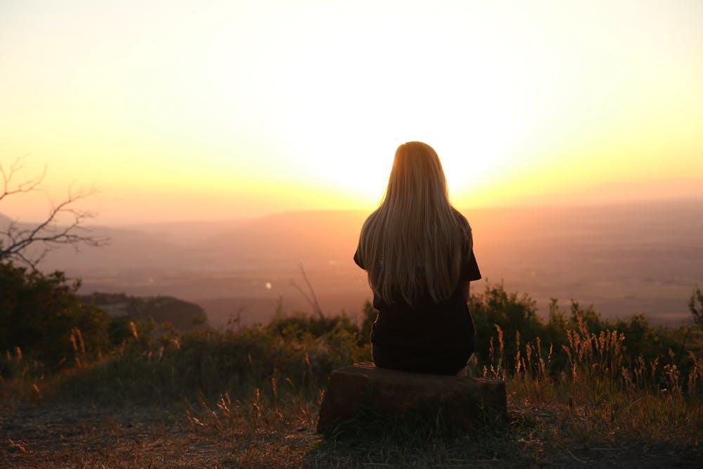 Mujer mirando el atardecer.  Imagen: Pexels