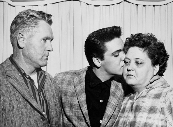 Elvis Presley kisses his mother, Gladys, on the eve of his induction into the Army. On the left is his father, Vernon. | Photo: Getty Images