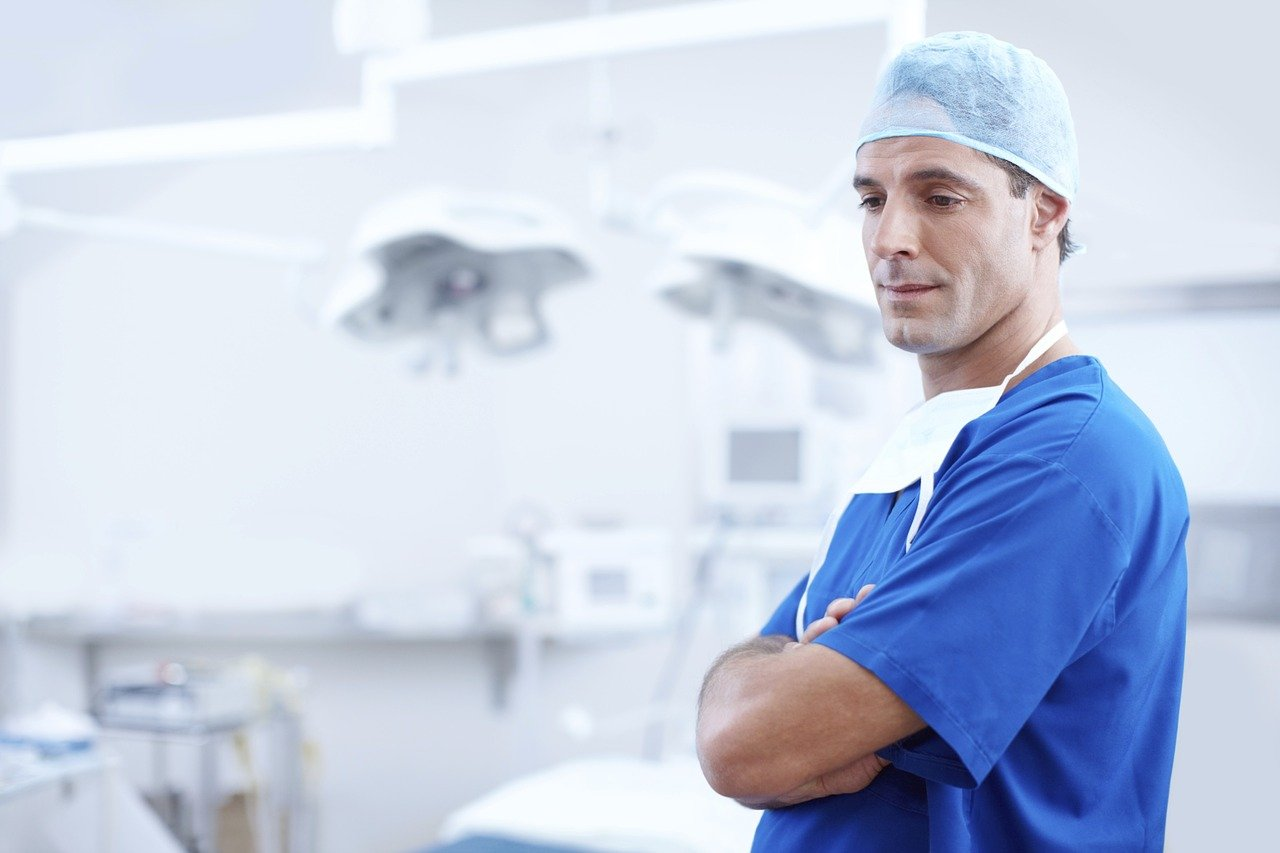 A doctor wearing blue scrubs with his hands folded at a hospital | Photo: Pixabay/Free-Photos
