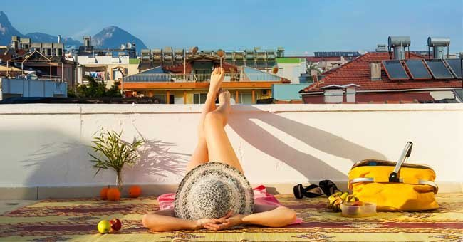 A woman sunbathing on a roof | Shutterstock.com