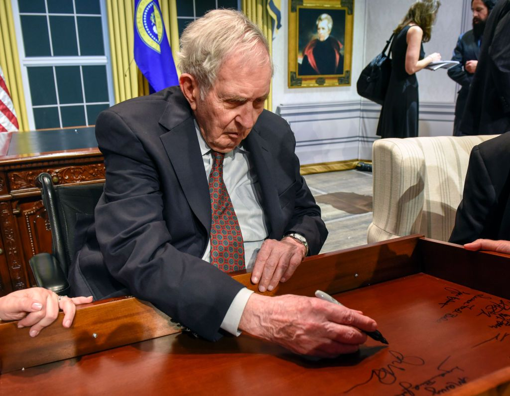 Lyon Gardiner Tyler Jr. signs his name on the inside of a desk drawer with other descendants of past Presidents gathered for a panel discussion at the Kennedy center, on August, 28, 2018 in Washington, DC | Photo: Getty Images