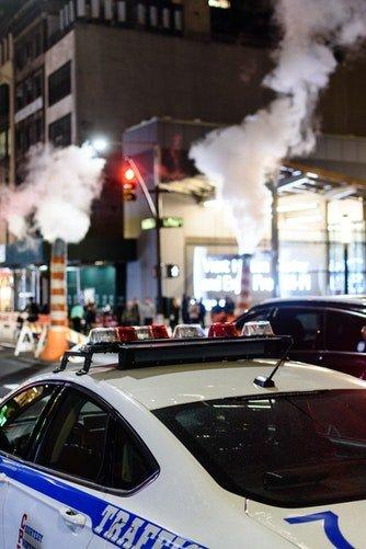 Voiture de police traversant la rue   Photo : Unsplash