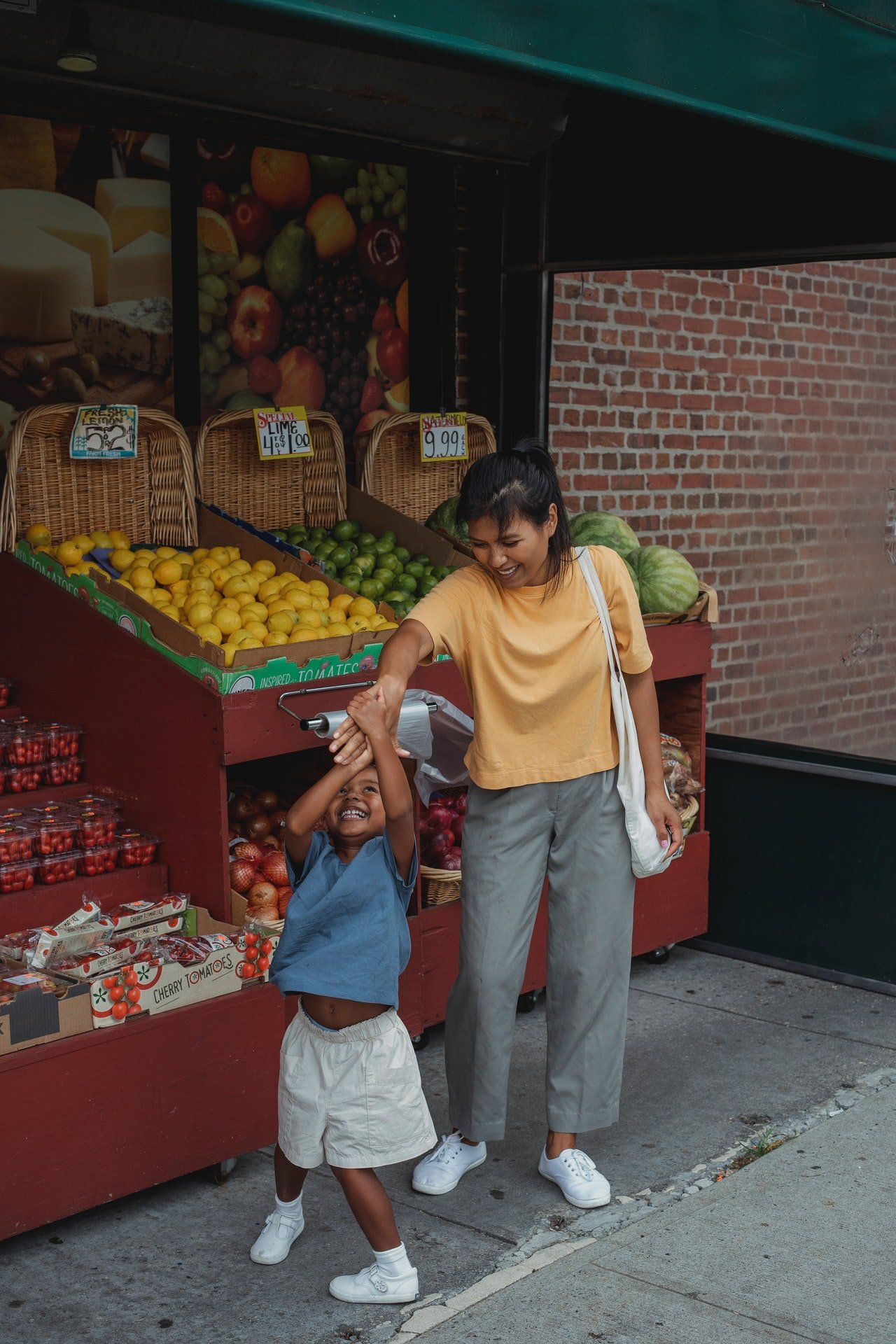 Woman and daughter in a fruit shop |  Photo: Pexels