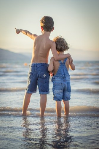 Deux enfants debout sur la plage | Photo : Pixabay