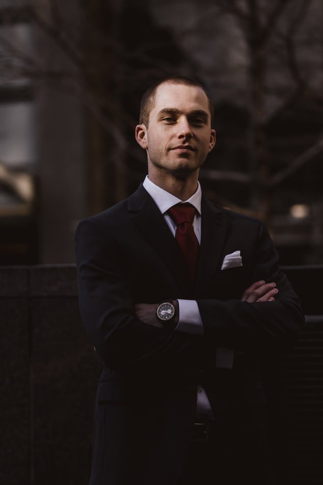 A man looking pleased in a suit   Photo: Unsplash