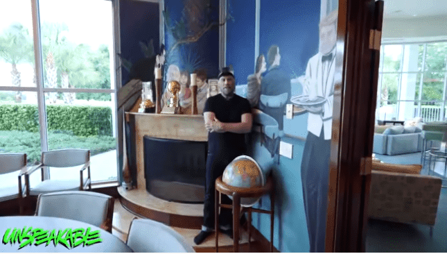 John Travolta posing in his dining room | Source: YouTube/Unspeakable