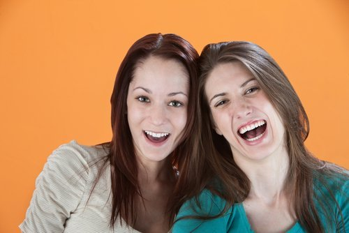 Two girlfriends laughing out loud. | Source: Shutterstock.