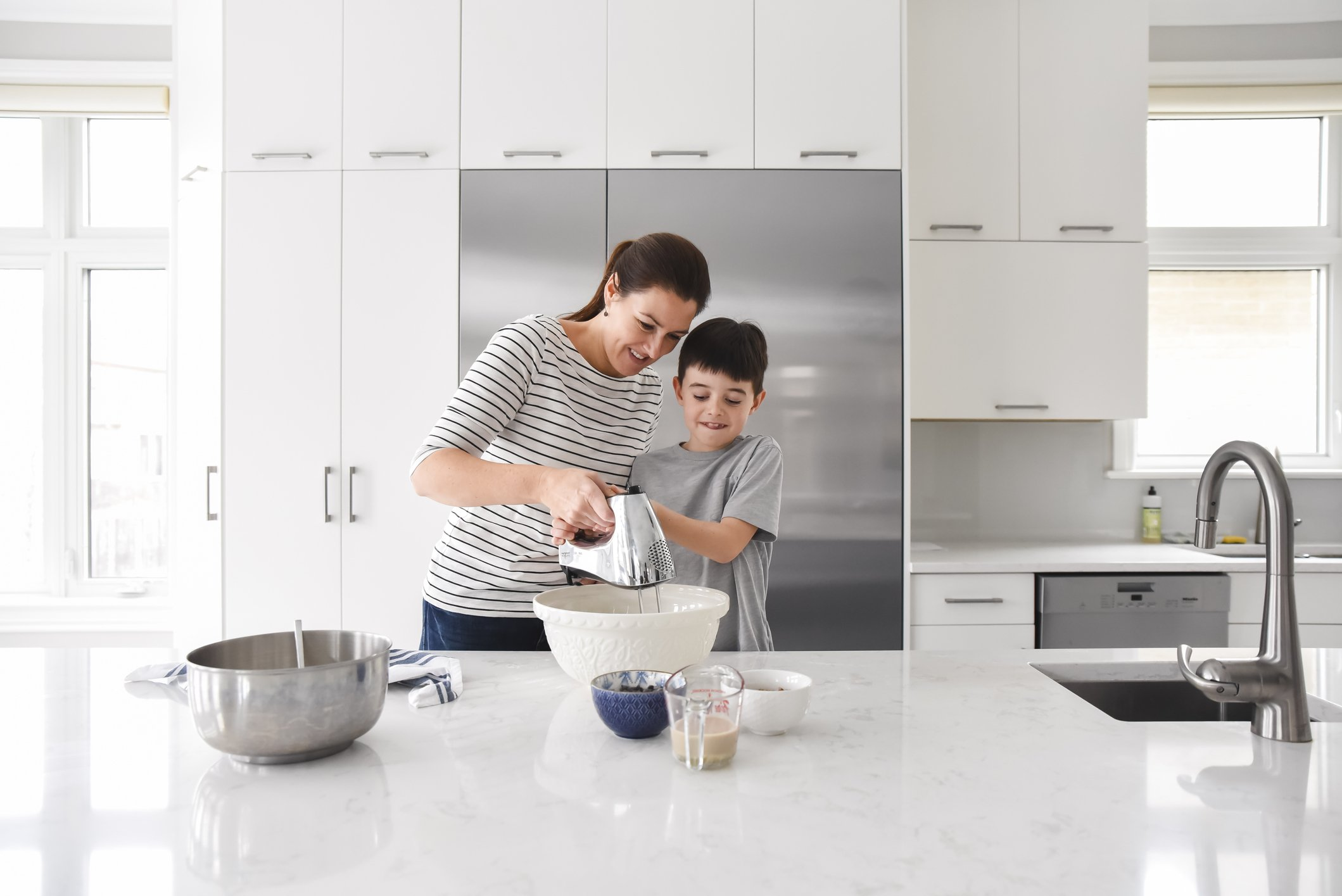Mother helping young son use a mixer while cooking in a modern kitchen | Photo: Getty Images