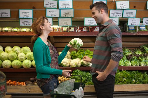 Photo of a man and woman chatting whilst shopping in a health food store | Photo: Getty Images