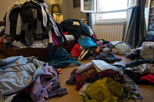 Photo of a messy bedroom with clothes and possessions scattered on the floor and bed | Photo: Getty Images
