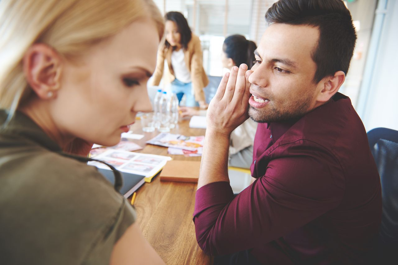 A couple telling secrets at work. | Source: Shutterstock