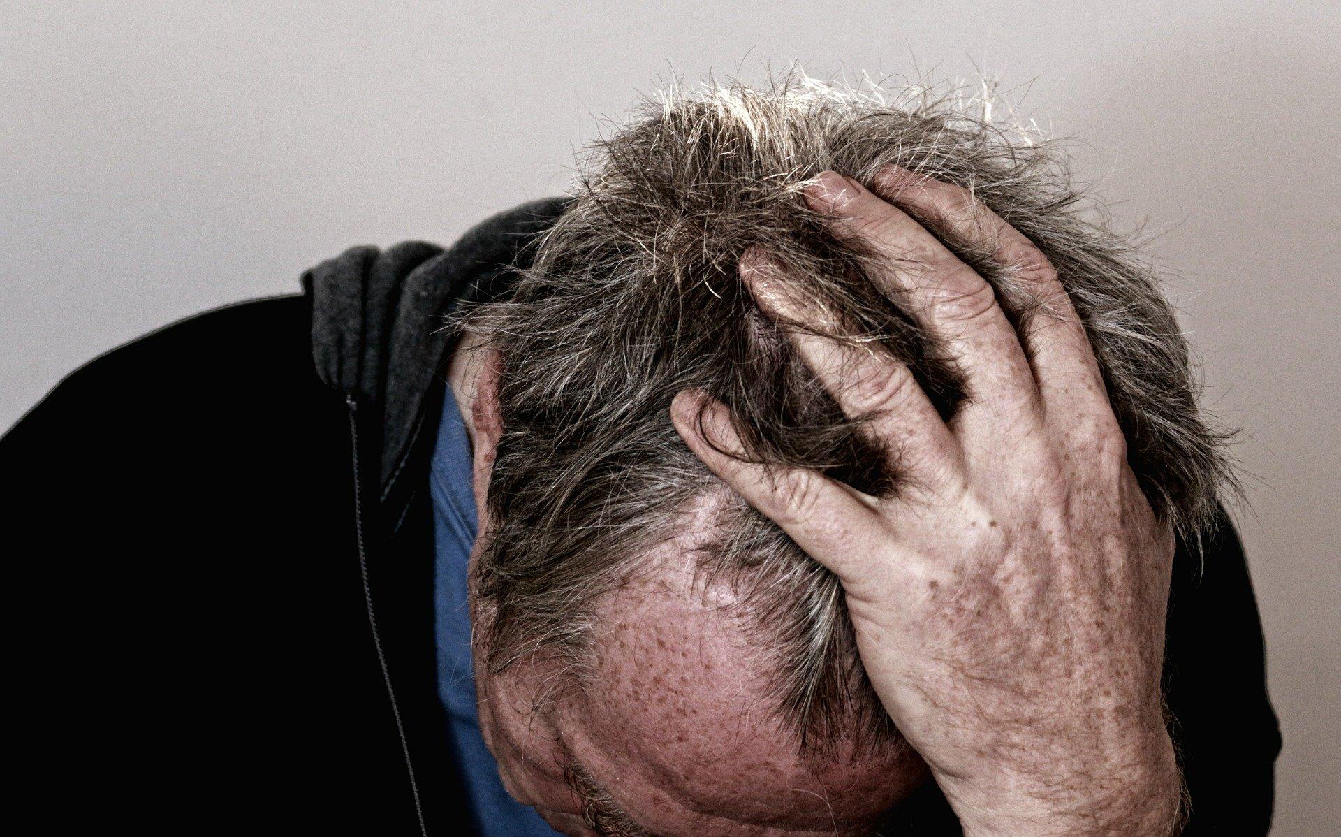 Man holding his head in despair.     Photo: Pixabay