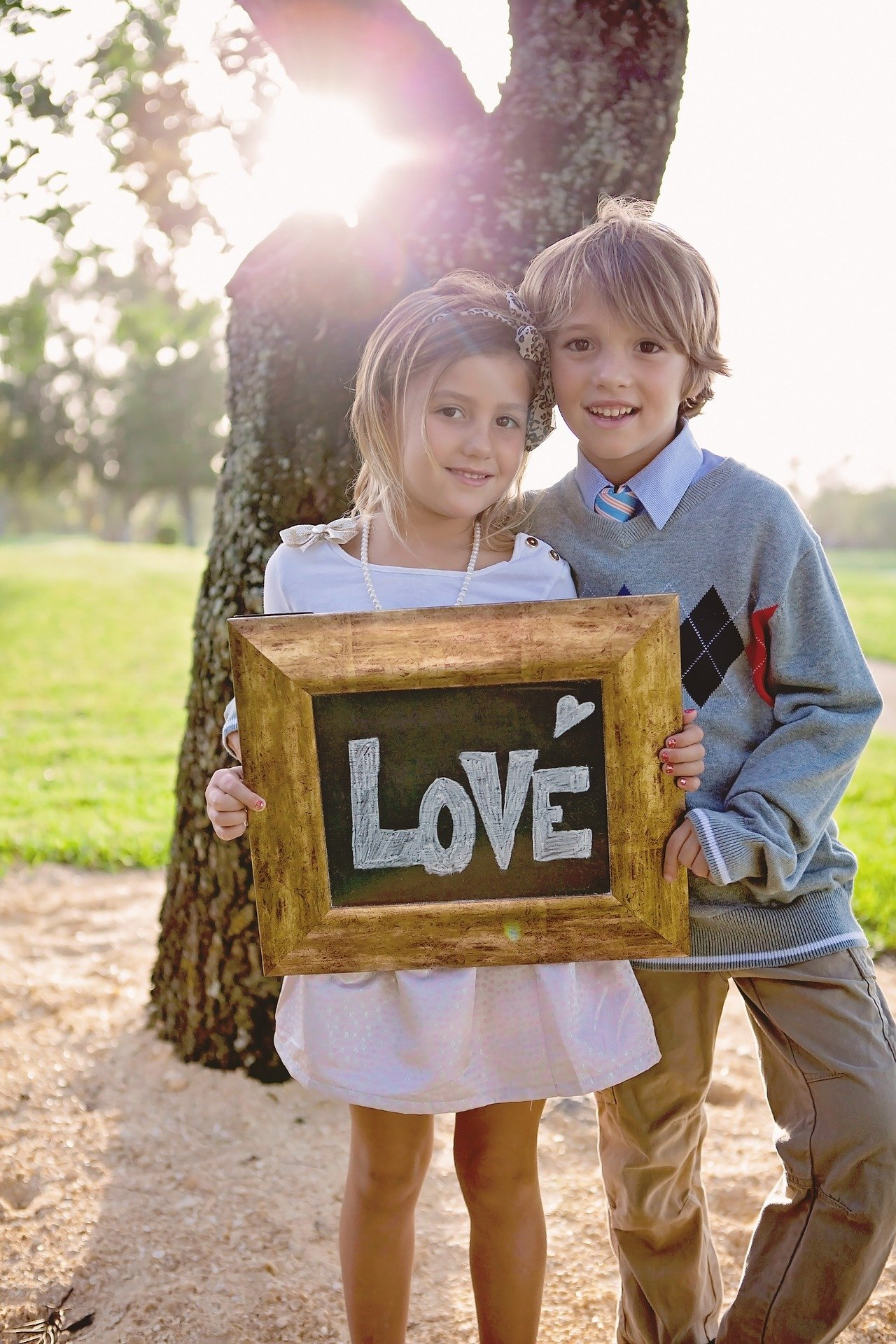 A photo of siblings holding a love frame. | Photo: Pixabay