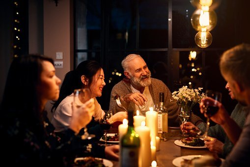 Cheerful guests at dinner table listening to friend and drinking wine | Photo: Getty Images