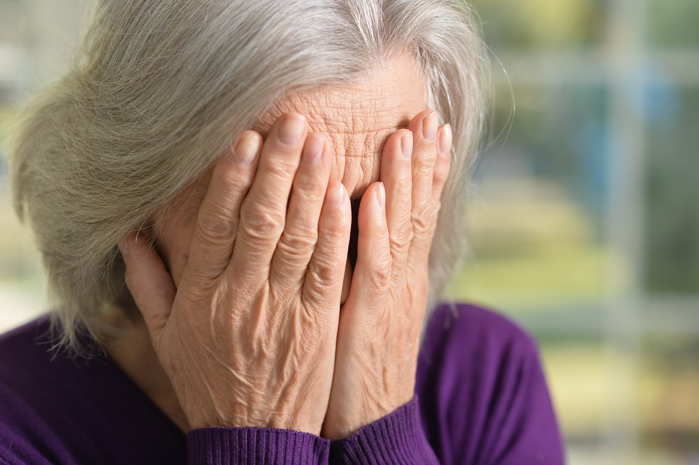 An old woman covers her face | Photo: Shutterstock