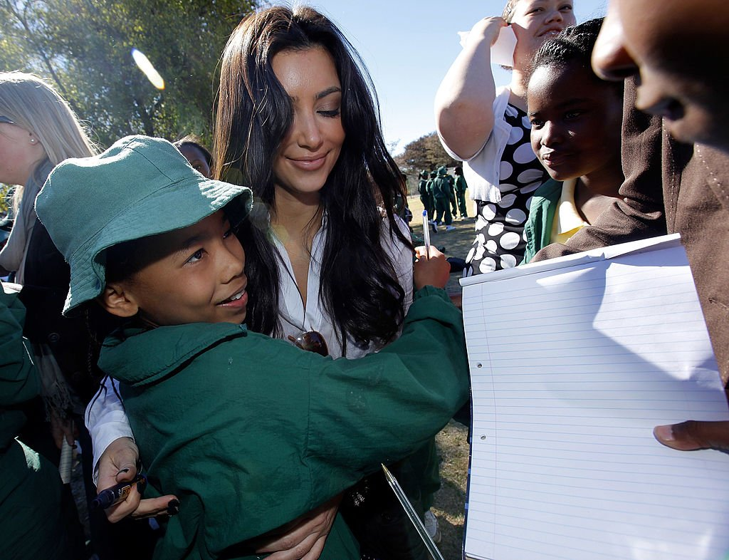 Kim Kardashian signs autographs for school children from the Acacia Primary School during a vist to the Acacia Primary school in Botswana , July 2009 | Source: Getty Images