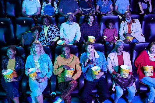 Photo of multi-ethnic audience enjoying popcorn while watching comedy movie at cinema hall | Photo: Getty Images
