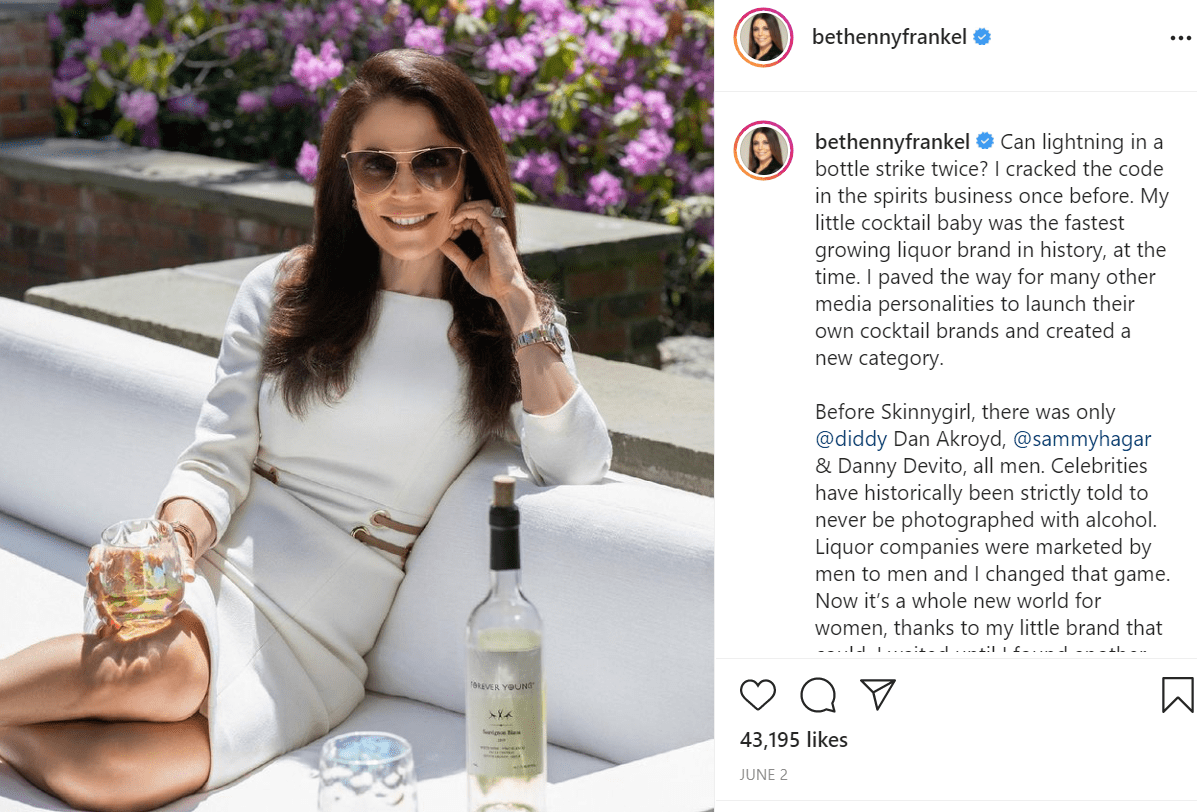 Pictured - Bethenny Frankel poses outdoors on a sunny day in a white dress sipping on her cocktail liquor brand   Source: Instagram/@bethennyfrankel