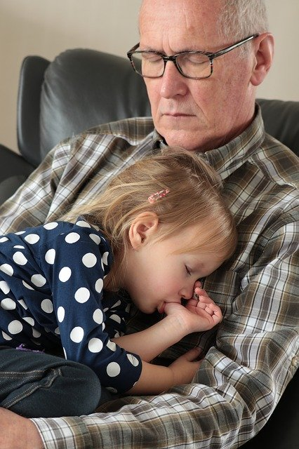 Young girl sleeps in elderly man's arms | Photo: Pixabay