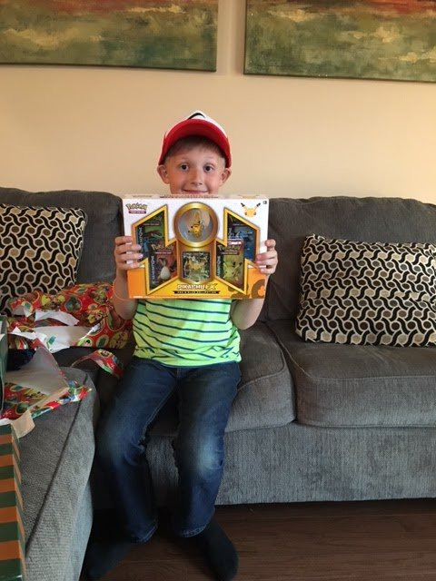 Mahlon proudly showing off one of his presents, a special deck of Pokémon cards   Photo: Kristen Layne/Life on Peanut Layne