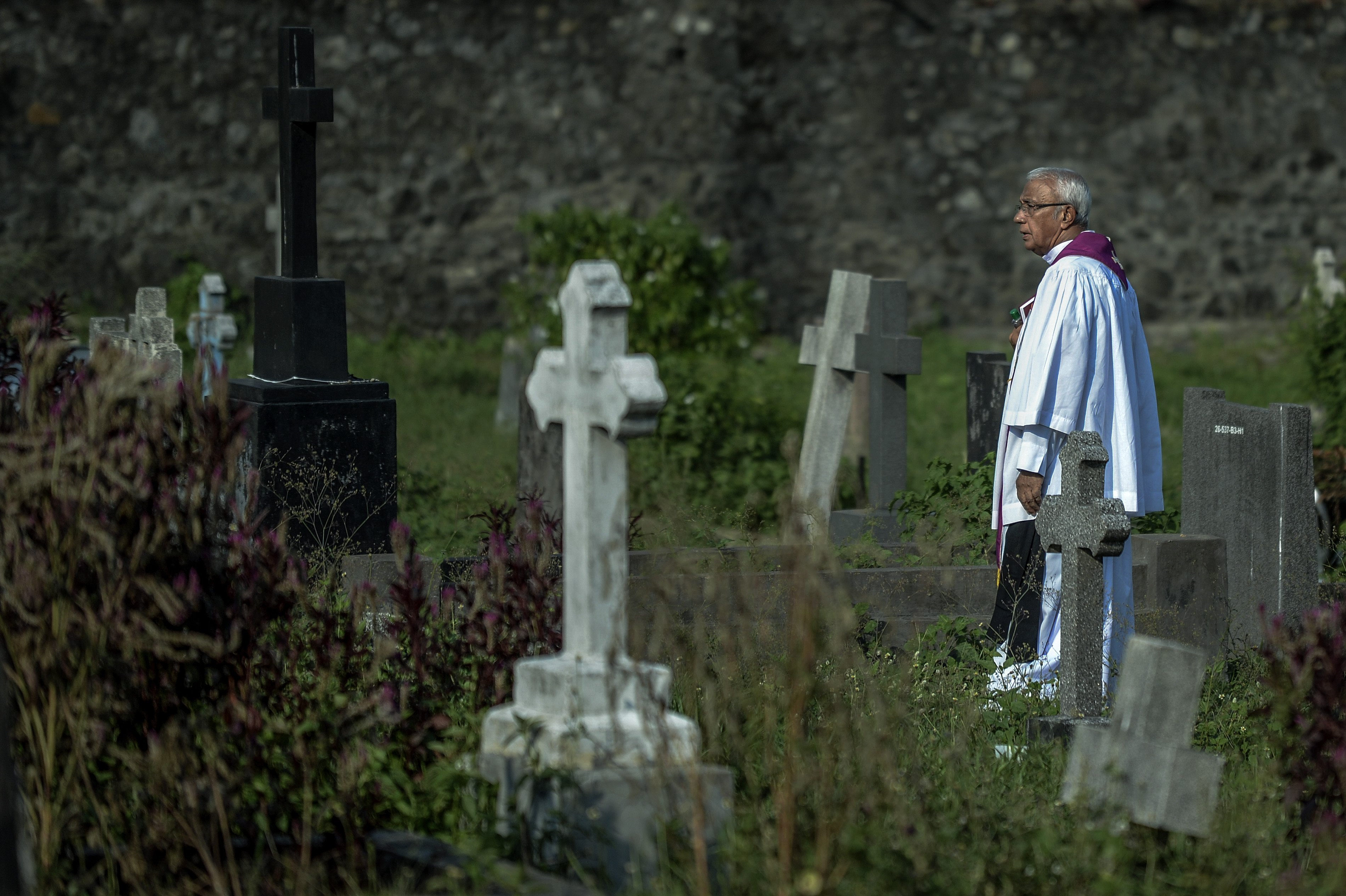 A priest waiting among the graves for the beginning of the burial of a victim of the Easter Sunday Bombings in Colombo, Sri Lanka | Photo: Getty Images