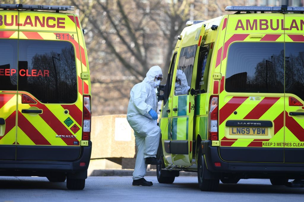 A member of the ambulance leading an unseen patient into an ambulance at St Thomas' Hospital in London on March 24, 2020. │Photo: Getty Images