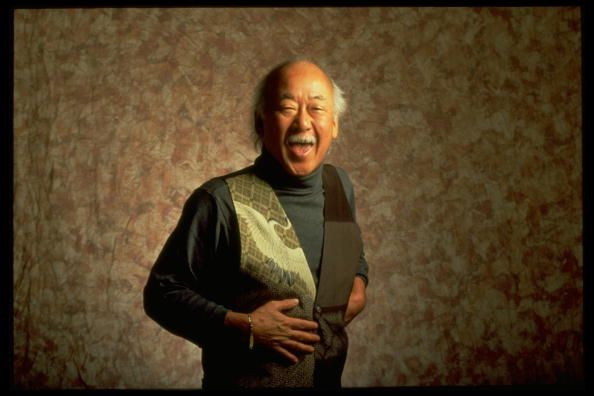 Actor Pat Morita laughing in front of nondescript backdrop | Photo: Getty Images