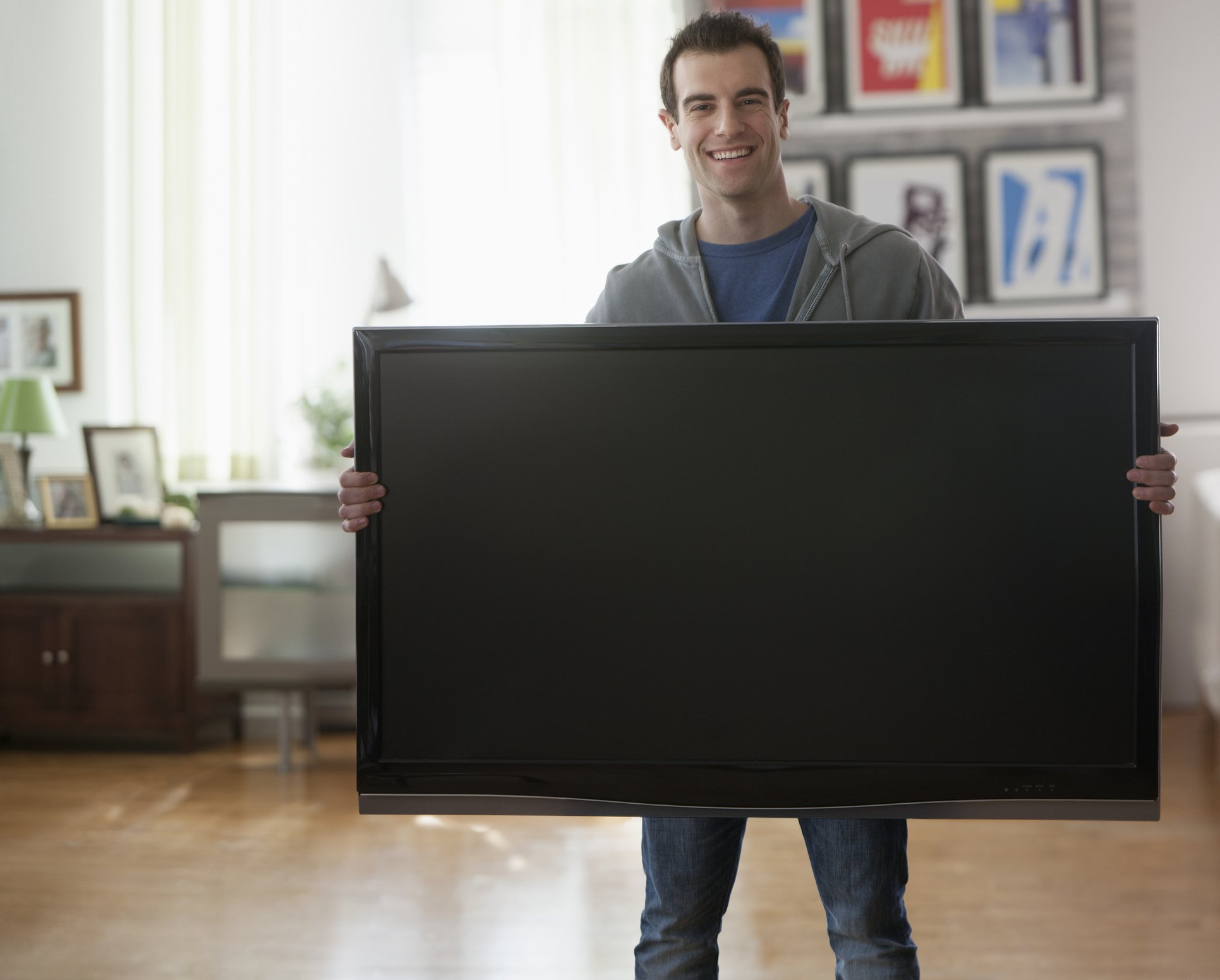 Photo of a young man carrying a TV | Photo: Getty Images