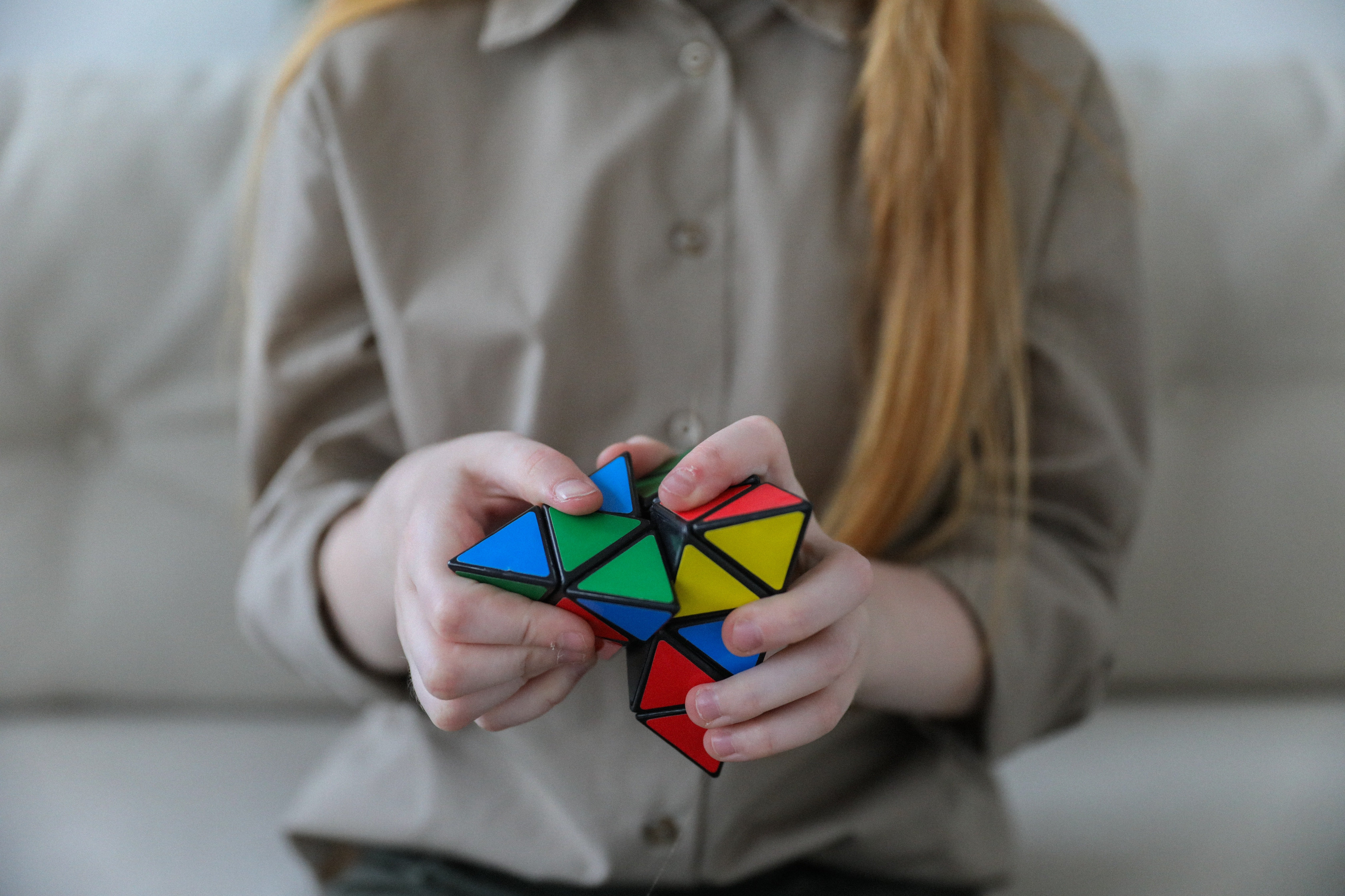 A girl holds a Rubix cube in her hands and it attempting to crack the code | Photo: Pexels