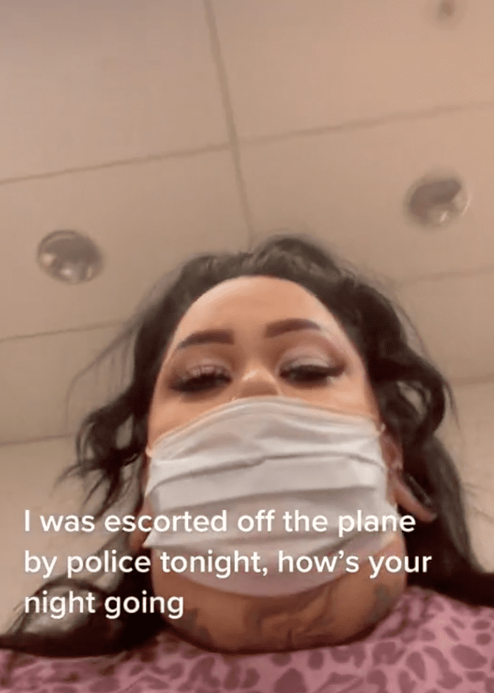 Woman records footage as she is escorted off of a plane by police officers   Photo: TikTok/fattrophywife
