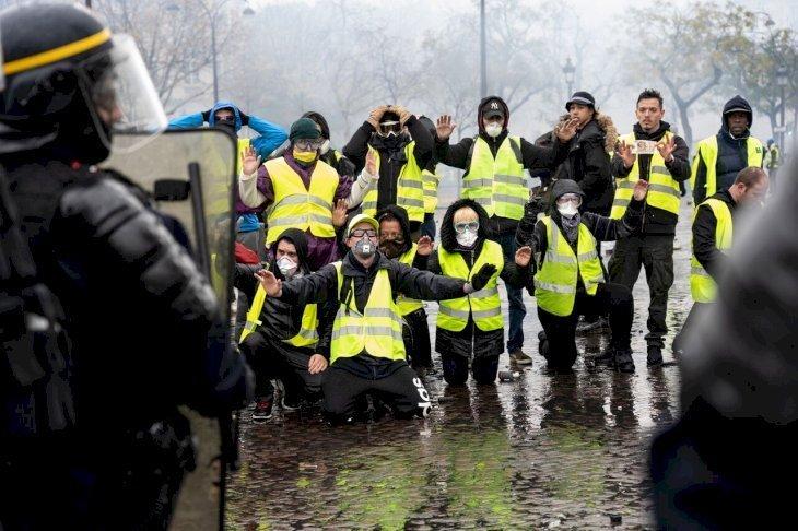 Des gilets jaunes mettant à genoux devant les CRS. l Source: Getty Images