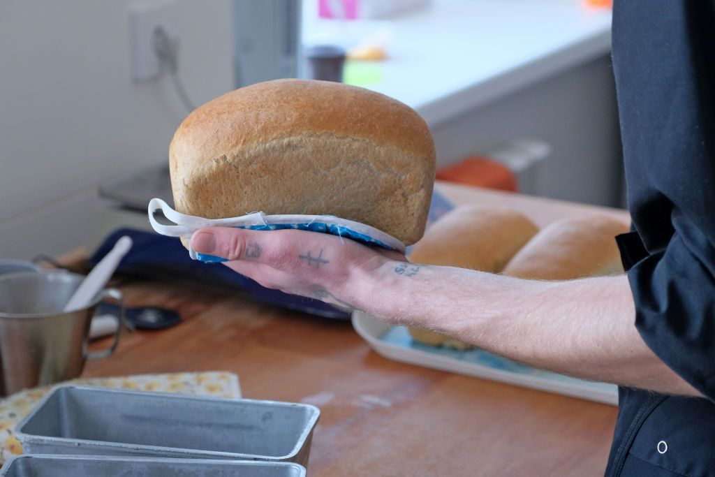 A man holding a loaf of bread.   Source: Shutterstock