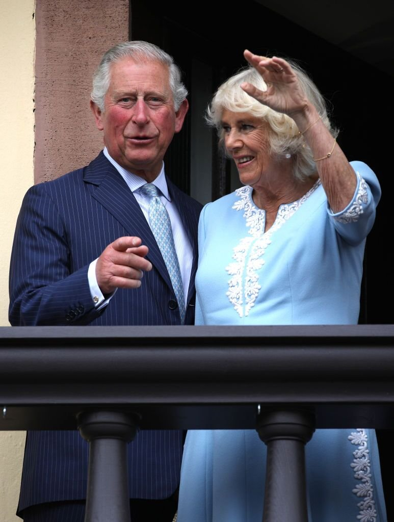 Prince Charles, Prince of Wales and Camilla, Duchess of Cornwall wave to the crowd from the balcony at Old City Hall. | Source: Getty Images
