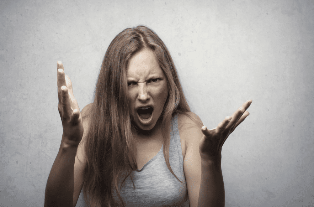 An angry woman in a grey vest with her hands up. | Photo: Pexels.