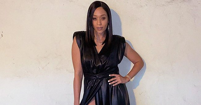 Tia Mowry Shows Major Leg in Leather Wrap Dress with Slit and White High-Heeled Boots in a Photo