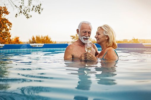 Photo of Senior couple enjoying summertime in a swimming pool | Photo: Getty Images