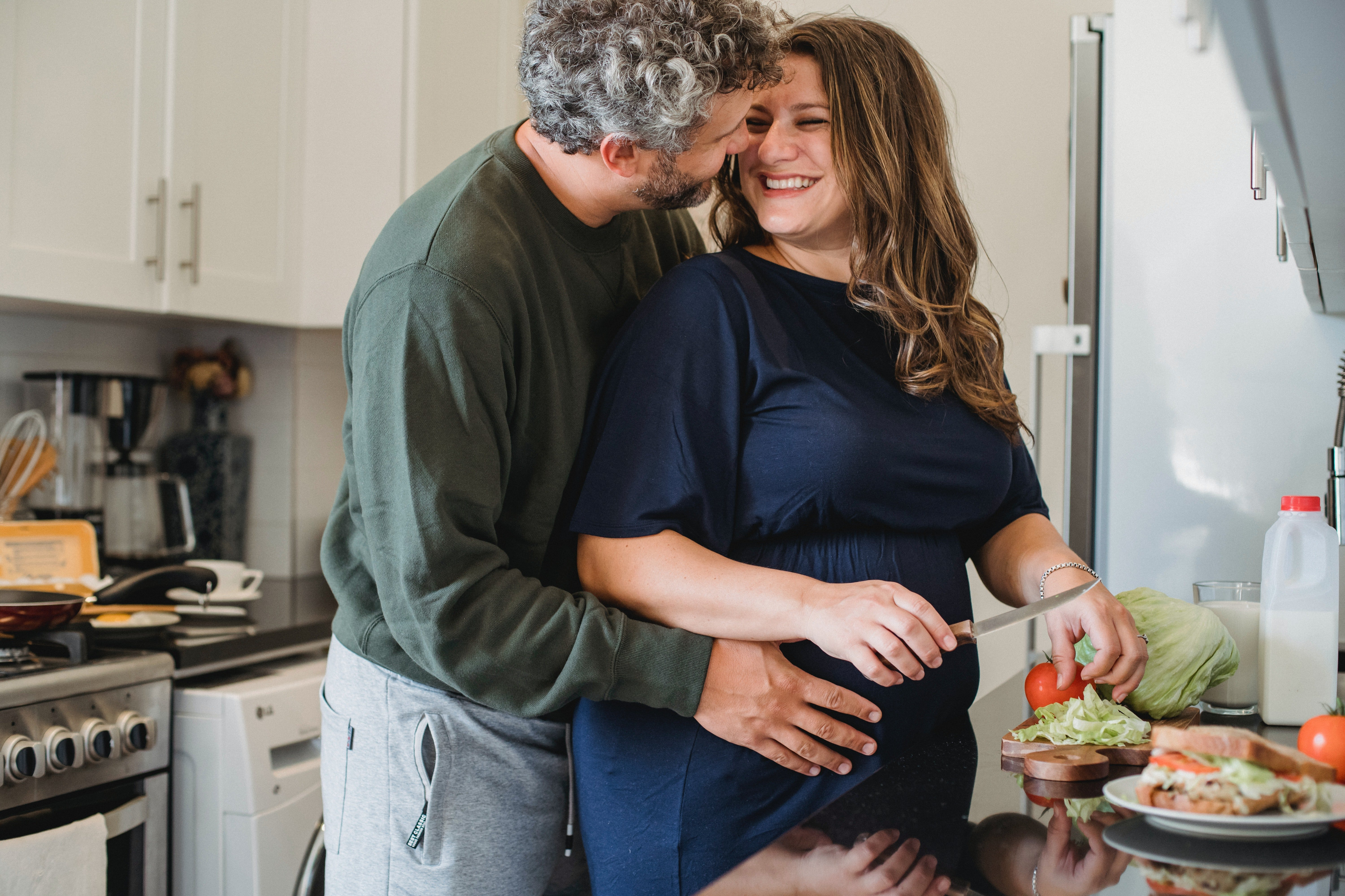 A husband lovingly embracing his pregnant wife while she's cooking.   Photo: Pexels/Amina Philkins