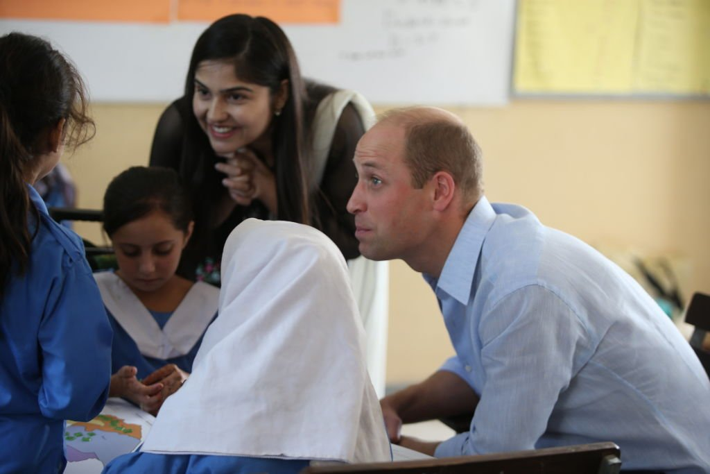 Prince William et Kate Middleton s'entretiennent avec des étudiants lors de la visite d'une école à Islamabad, au Pakistan. | Photo: Getty Images