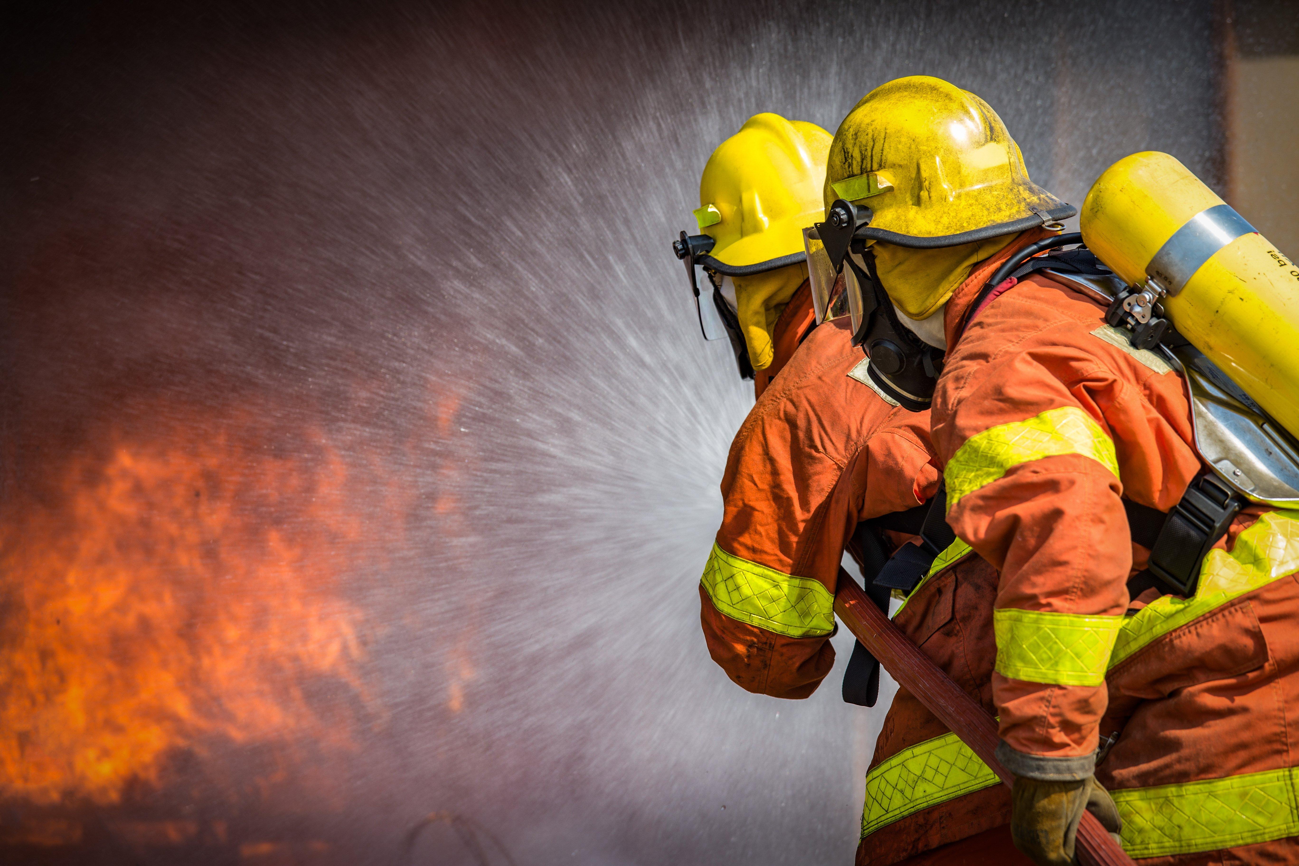 Deux pompiers en train d'éteindre un feu | photo : shutterstock