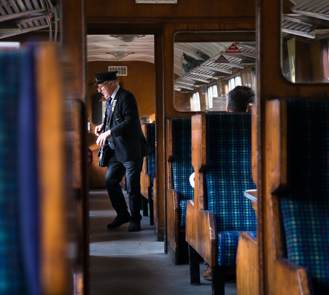 The train conductor is checking people's tickets. | Photo: Unsplash/Johnny Rothwell