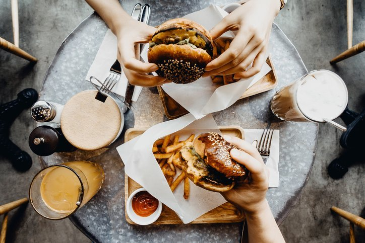 Friends having a good time eating burgers with french fries and drinks in a cafe | Photo: Getty Images