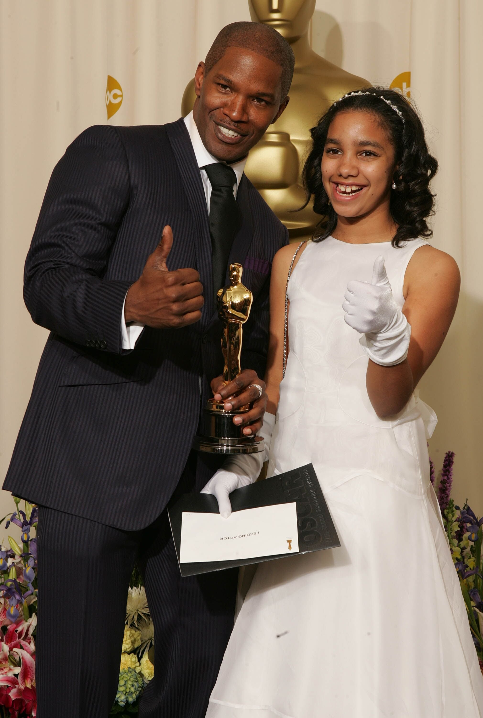 """Jamie Foxx poses with his """"Best Actor in a Leading Role"""" award for """"Ray"""" with his daughter Corrine Marie Foxx backstage during the 77th Annual Academy Awards in 2005 