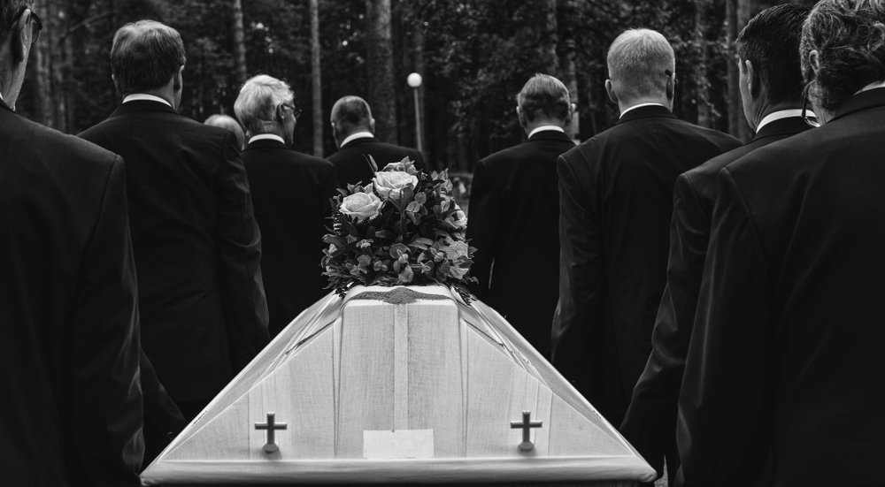 A photo of a funeral procession and coffin. | Photo: Shutterstock.