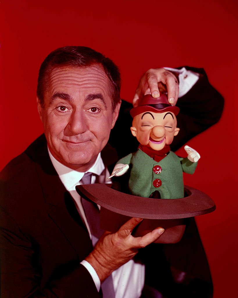 Jim Backus (1913-1989), US actor, holding a puppet of cartoon character 'Mr Magoo', in a studio portrait against a red background, circa 1965 | Photo: Getty Images